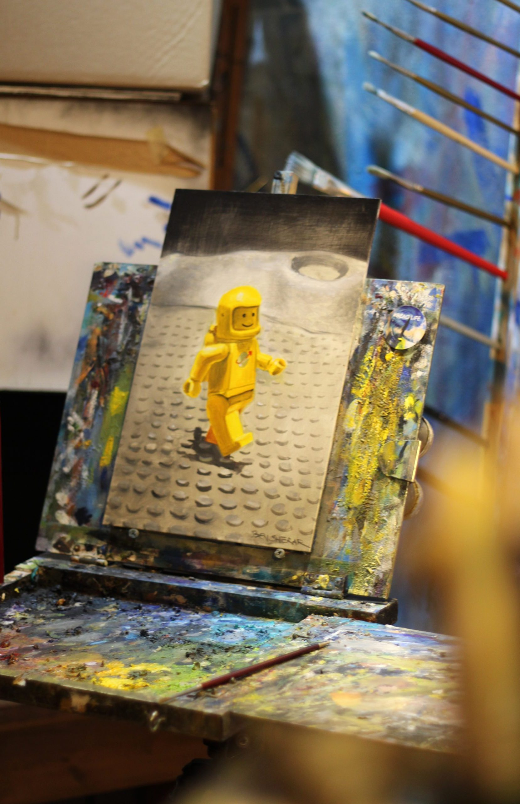 Still life painting of a toy spaceman on the easel by Ben Sherar