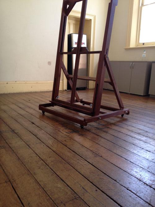 A wooden artists easel inside an art studio