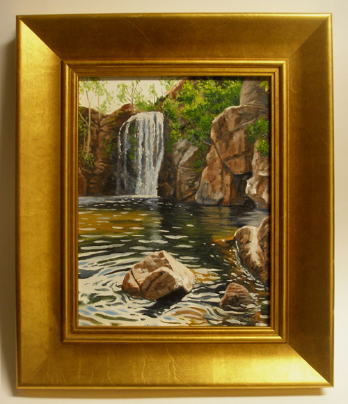 A framed oil painting of a waterfall