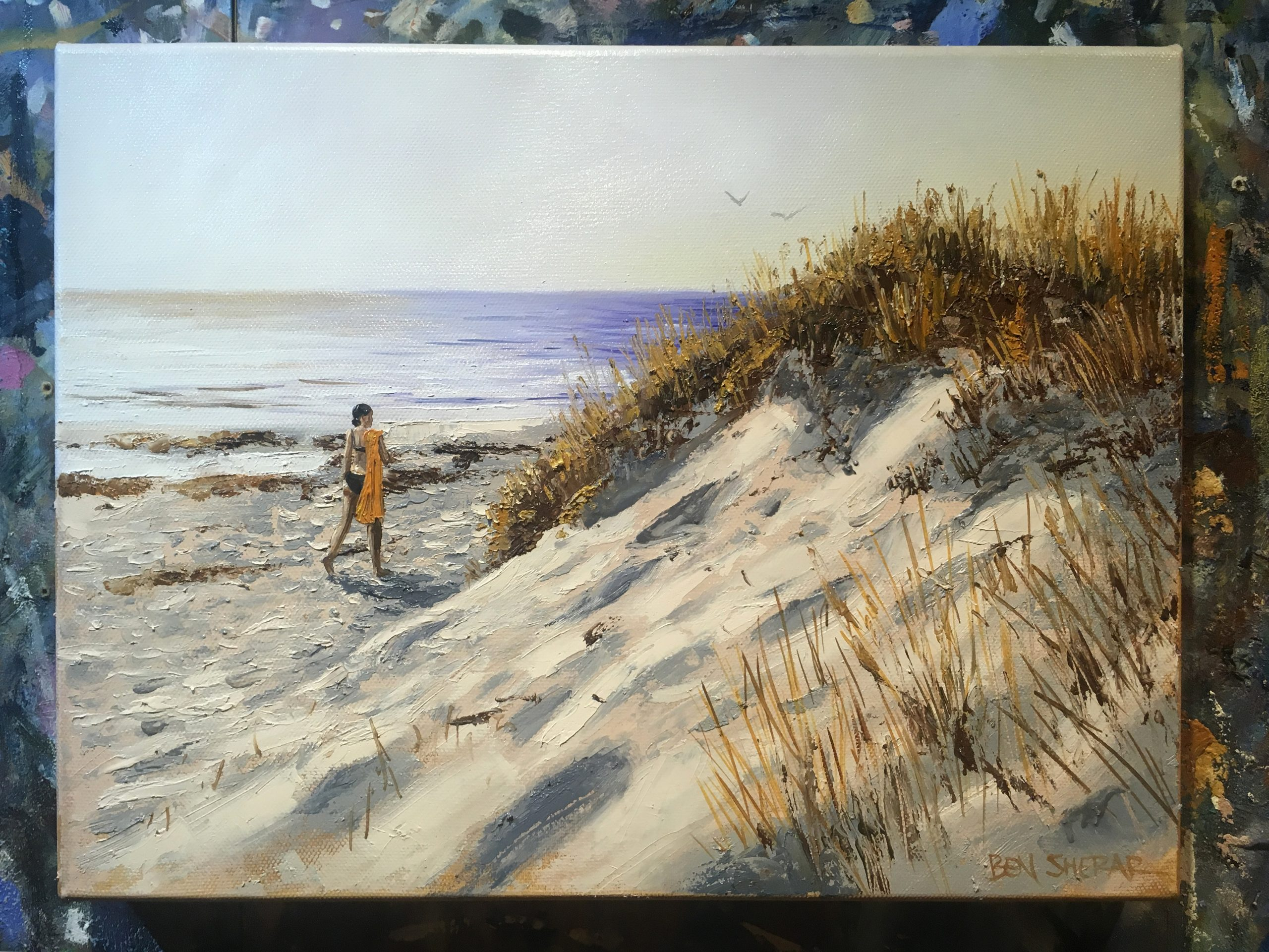 An original oil painting of a woman walking on a beach at sunset by artists Ben Sherar