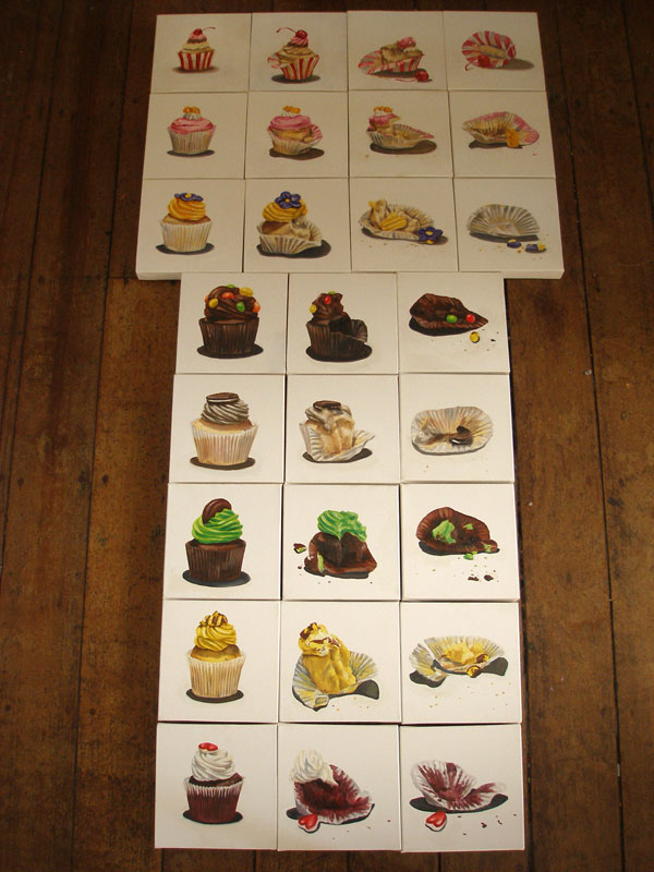 A series of painting of cupcakes laid out on the floor
