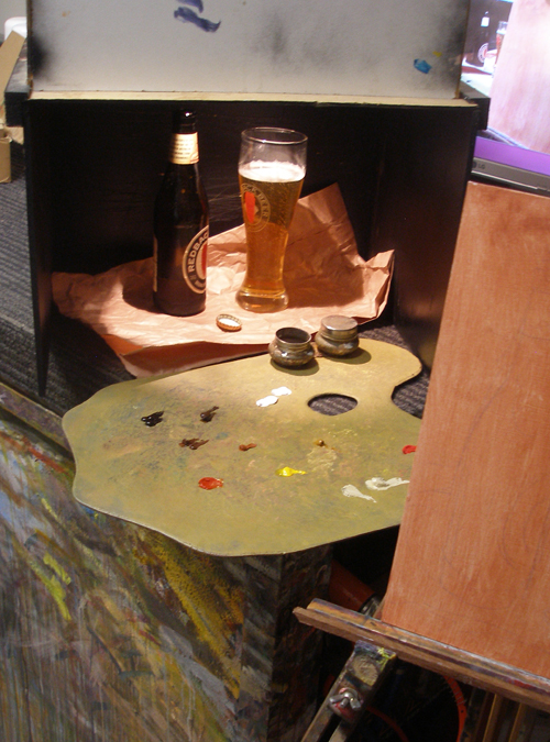 A still life painting setup with a beer bottle
