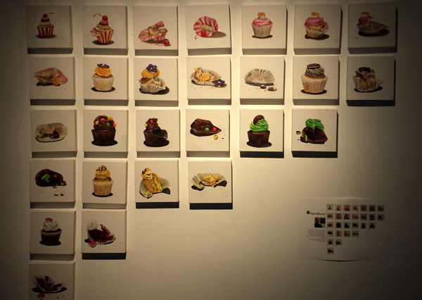 A wall with lots of paintings of cupcakes