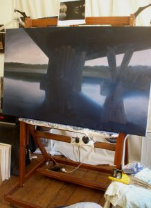 A progress photo of an unfinished night painting on an artists easel